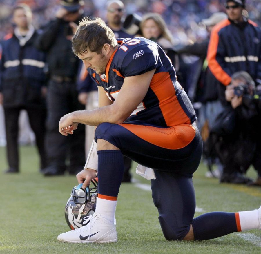 Tim Tebow kneels during a Bronco football game, in an effort to represent his faith. PHOTO // bostonglobe.com