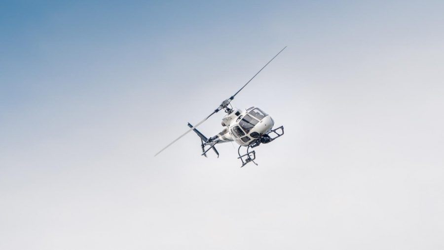 A helicopter flies high above Stewart Hall.